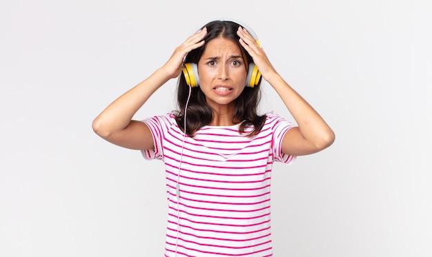 Junge hispanische frau, die sich gestresst, ängstlich oder verängstigt fühlt, mit den händen auf dem kopf musik mit kopfhörern hört