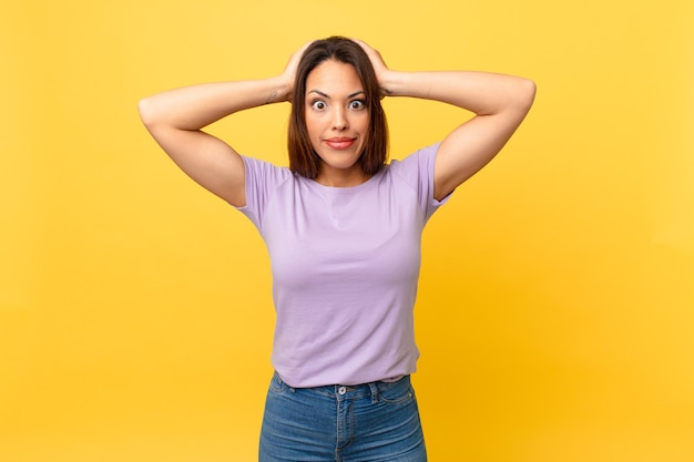 Junge hispanische frau, die sich gestresst, ängstlich oder verängstigt fühlt, mit den händen auf dem kopf