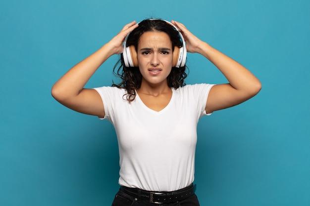Junge hispanische frau, die sich gestresst, besorgt, ängstlich oder ängstlich fühlt, mit händen auf dem kopf, die bei einem fehler in panik geraten