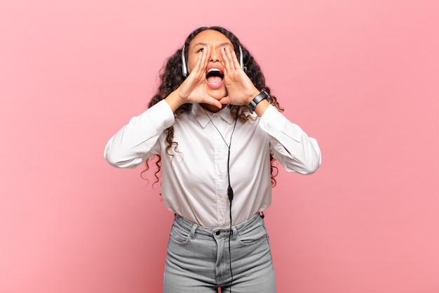 Junge hispanische frau, die sich glücklich, aufgeregt und positiv fühlt, mit den händen neben dem mund einen großen schrei ausspricht und ruft. telemarketing-konzept