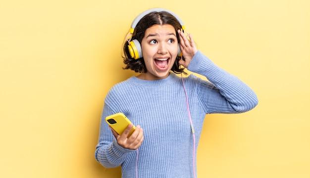 Junge hispanische frau, die sich glücklich, aufgeregt und überrascht fühlt. kopfhörer- und smartphone-konzept