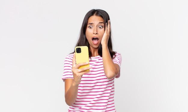 Junge hispanische frau, die sich glücklich, aufgeregt und überrascht fühlt und ein smartphone hält