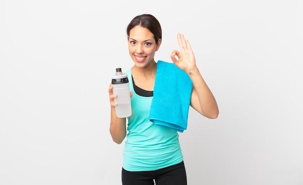 Junge hispanische frau, die sich glücklich fühlt und zustimmung mit okayer geste zeigt. fitnesskonzept