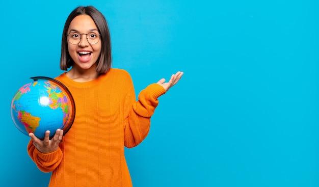 Junge hispanische frau, die sich glücklich, überrascht und fröhlich fühlt, mit positiver einstellung lächelt und eine lösung oder idee realisiert