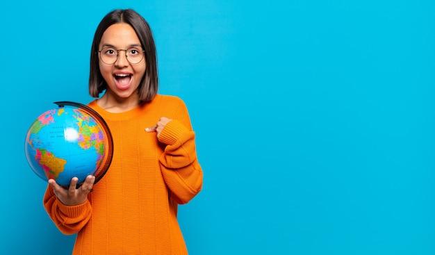Junge hispanische frau, die sich glücklich, überrascht und stolz fühlt und mit einem aufgeregten, erstaunten blick auf sich selbst zeigt