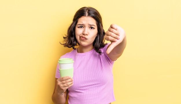 Junge hispanische frau, die sich kreuz fühlt und daumen nach unten zeigt. kaffee zum mitnehmen konzept