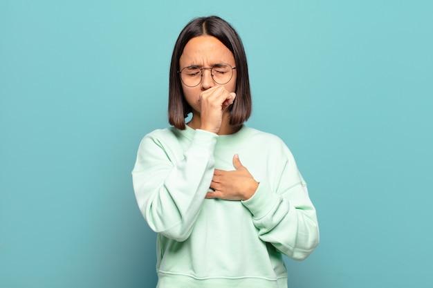 Junge hispanische frau, die sich mit halsschmerzen und grippesymptomen krank fühlt und mit bedecktem mund hustet