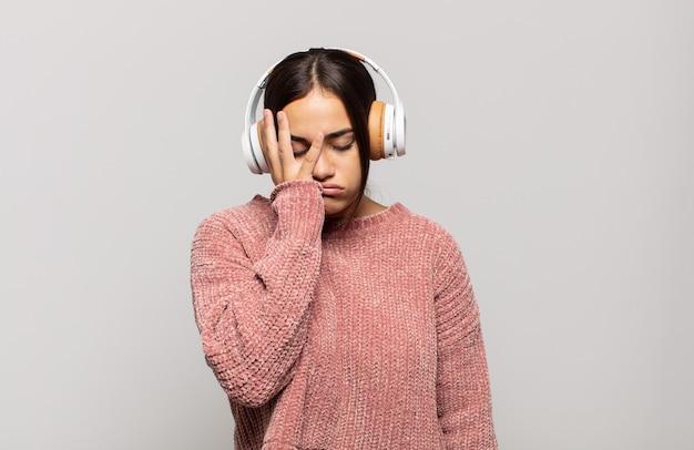 Junge hispanische frau, die sich nach einer ermüdenden, langweiligen und mühsamen aufgabe gelangweilt, frustriert und schläfrig fühlt und gesicht mit hand hält