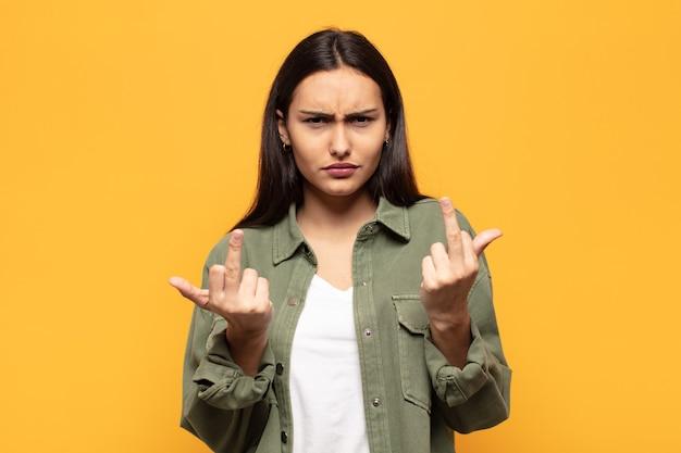 Junge hispanische frau, die sich provokativ, aggressiv und obszön fühlt und den mittelfinger mit einer rebellischen haltung bewegt