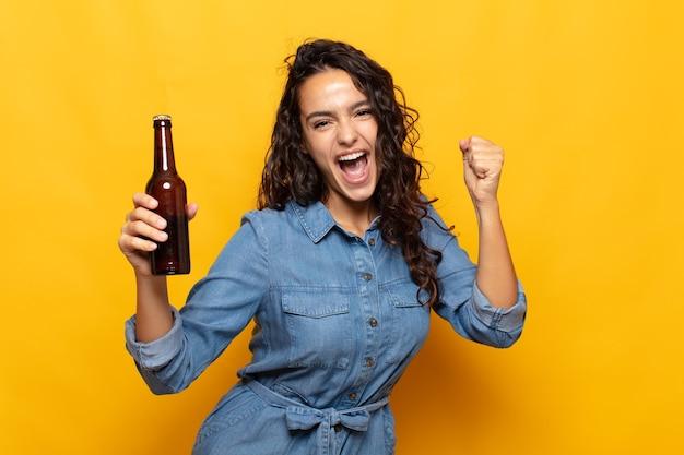 Junge hispanische frau, die sich schockiert, aufgeregt und glücklich fühlt, lacht und erfolg feiert und wow sagt!