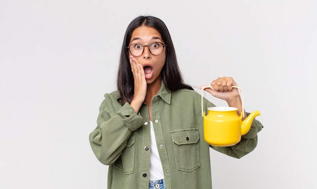 Junge hispanische frau, die sich schockiert und verängstigt fühlt und eine teekanne hält