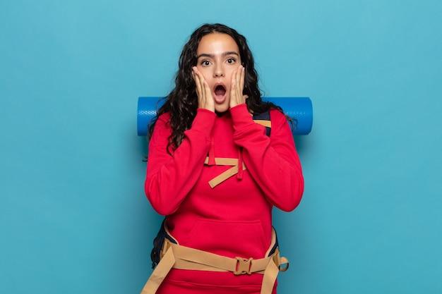 Junge hispanische frau, die sich schockiert und verängstigt fühlt und mit offenem mund und händen auf den wangen erschrocken aussieht