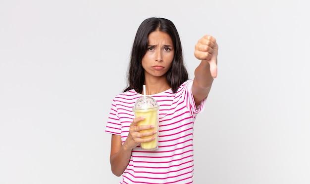 Junge hispanische frau, die sich überquert, daumen nach unten zeigt und einen vanila-smoothy-milchshake hält