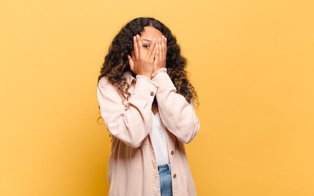 Junge hispanische frau, die sich verängstigt oder verlegen fühlt, mit halb mit händen bedeckten augen späht oder ausspioniert
