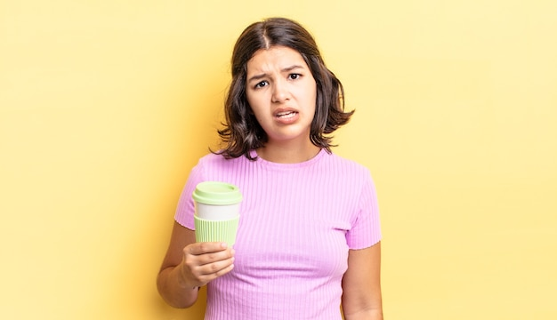 Junge hispanische frau, die sich verwirrt und verwirrt fühlt. kaffee zum mitnehmen konzept