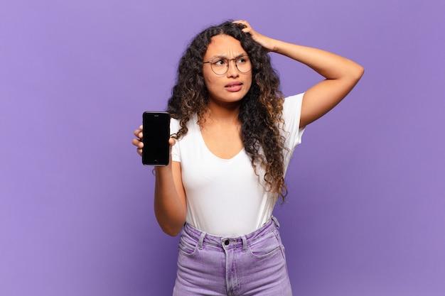 Junge hispanische frau, die sich verwirrt und verwirrt fühlt, sich am kopf kratzt und zur seite schaut. smartphone-konzept