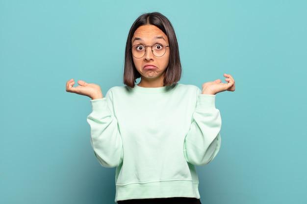 Junge hispanische frau, die sich verwirrt und verwirrt fühlt, zweifelt, gewichtet oder verschiedene optionen mit lustigem ausdruck wählt