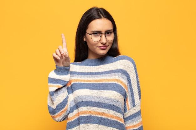 Junge hispanische frau, die sich wie ein genie fühlt, das stolz den finger in die luft hält, nachdem sie eine großartige idee realisiert hat, und sagt heureka