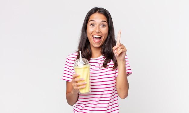 Junge hispanische frau, die sich wie ein glückliches und aufgeregtes genie fühlt, nachdem sie eine idee realisiert hat und einen vanille-smoothy-milchshake hält