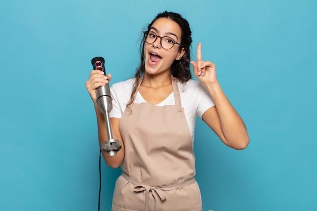 Junge hispanische frau, die sich wie ein glückliches und aufgeregtes genie fühlt, nachdem sie eine idee verwirklicht hat, fröhlich den finger hebend, eureka!