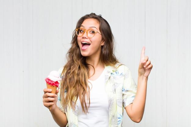 Junge hispanische frau, die sich wie ein glückliches und aufgeregtes genie fühlt, nachdem sie eine idee verwirklicht hat, fröhlich finger hebend, eureka!