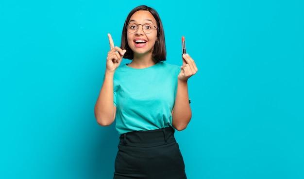 Junge hispanische frau, die sich wie ein glückliches und aufgeregtes genie fühlt, nachdem sie eine idee verwirklicht hat und fröhlich den finger hebt, heureka!
