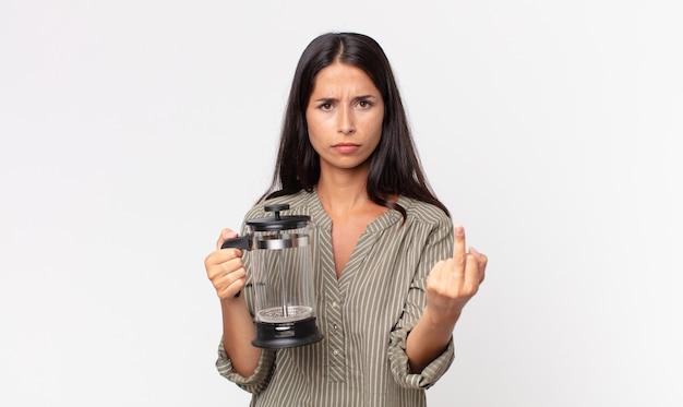 Junge hispanische frau, die sich wütend, verärgert, rebellisch und aggressiv fühlt und eine manuelle kaffeemaschine hält