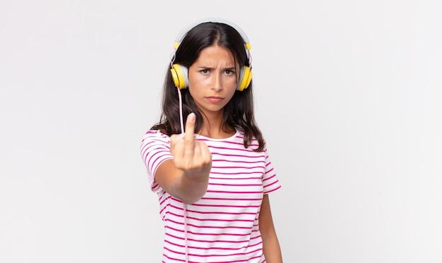 Junge hispanische frau, die sich wütend, verärgert, rebellisch und aggressiv fühlt und musik mit kopfhörern hört