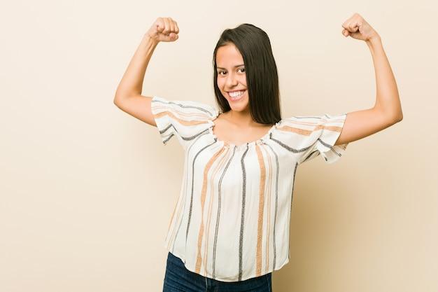 Junge hispanische frau, die stärkegeste mit den armen, symbol der weiblichen energie zeigt