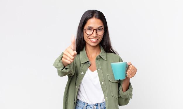 Junge hispanische frau, die stolz ist, positiv mit daumen nach oben lächelt und eine kaffeetasse hält