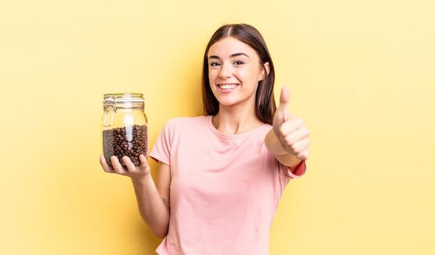 Junge hispanische frau, die stolz ist und positiv mit daumen nach oben lächelt. kaffeebohnen-konzept