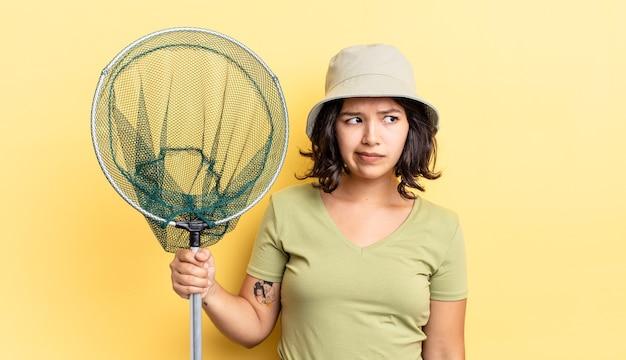 Junge hispanische frau, die traurig, verärgert oder wütend ist und zur seite schaut. fischernetzkonzept