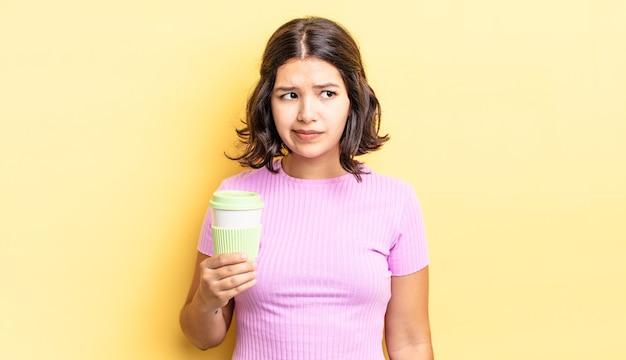 Junge hispanische frau, die traurig, verärgert oder wütend ist und zur seite schaut. kaffee zum mitnehmen konzept