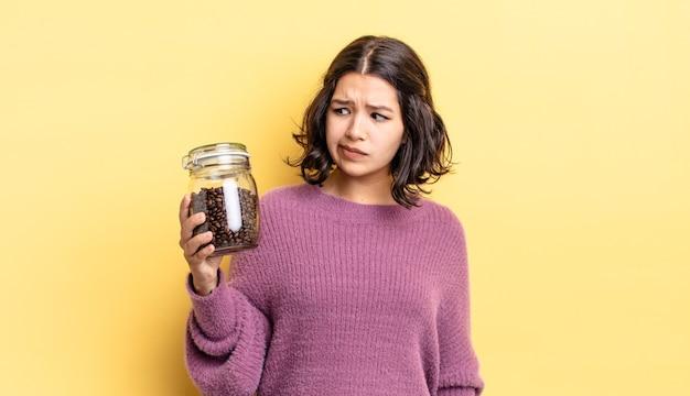 Junge hispanische frau, die traurig, verärgert oder wütend ist und zur seite schaut. kaffeebohnen-konzept