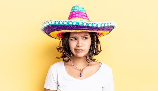 Junge hispanische frau, die traurig, verärgert oder wütend ist und zur seite schaut. mexikanisches hutkonzept