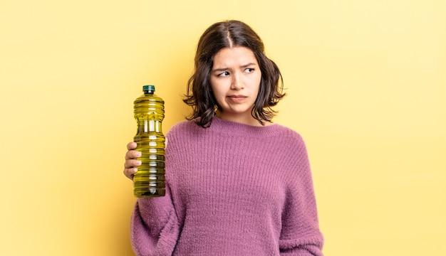 Junge hispanische frau, die traurig, verärgert oder wütend ist und zur seite schaut. olivenöl konzept