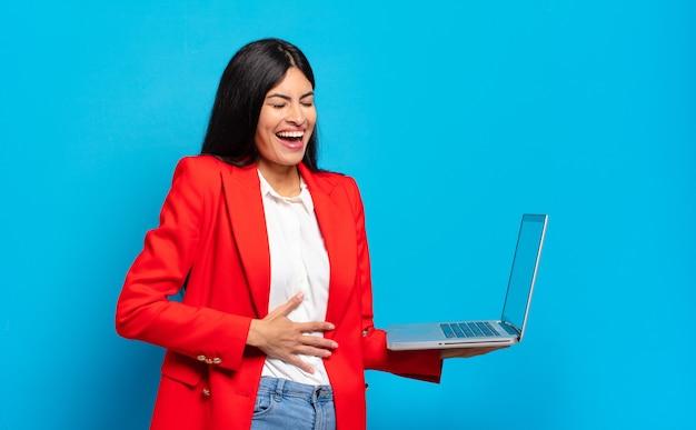 Junge hispanische frau, die über einen lustigen witz laut lacht, sich glücklich und fröhlich fühlt und spaß hat. laptop-konzept