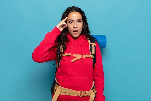 Junge hispanische frau, die überrascht, mit offenem mund, schockiert aussieht und einen neuen gedanken, eine neue idee oder ein neues konzept verwirklicht