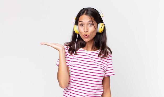Junge hispanische frau, die überrascht und schockiert aussieht, mit heruntergefallenem kiefer, die ein objekt hält, das musik mit kopfhörern hört