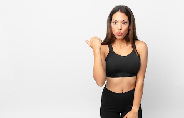 Junge hispanische frau, die ungläubig überrascht schaut. fitnesskonzept