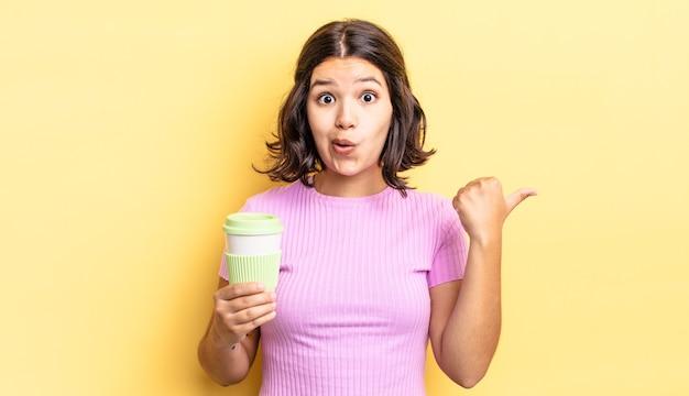 Junge hispanische frau, die ungläubig überrascht schaut. kaffee zum mitnehmen konzept