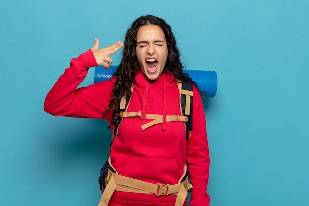 Junge hispanische frau, die unglücklich und gestresst aussieht, selbstmordgeste, die gewehrzeichen mit hand macht und auf kopf zeigt