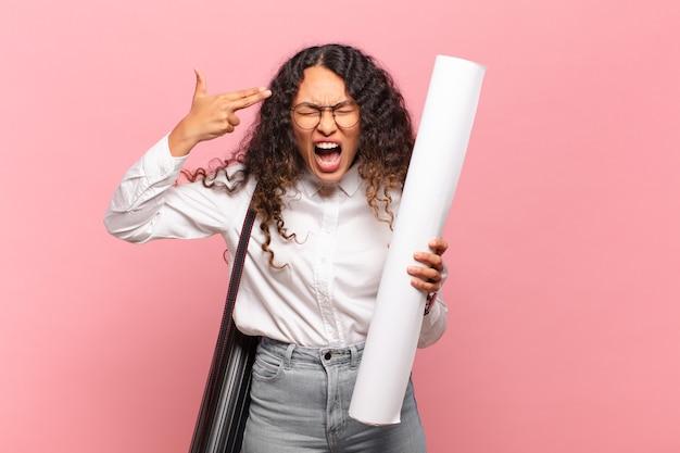 Junge hispanische frau, die unglücklich und gestresst aussieht, selbstmordgeste, die waffenzeichen mit der hand macht und auf den kopf zeigt. architektenkonzept