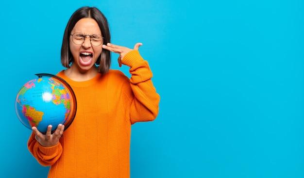 Junge hispanische frau, die unglücklich und gestresst aussieht, selbstmordgeste, die waffenzeichen mit der hand macht und auf den kopf zeigt