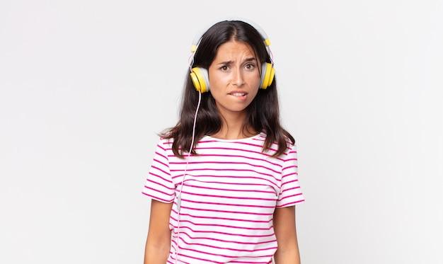 Junge hispanische frau, die verwirrt und verwirrt aussieht und musik mit kopfhörern hört
