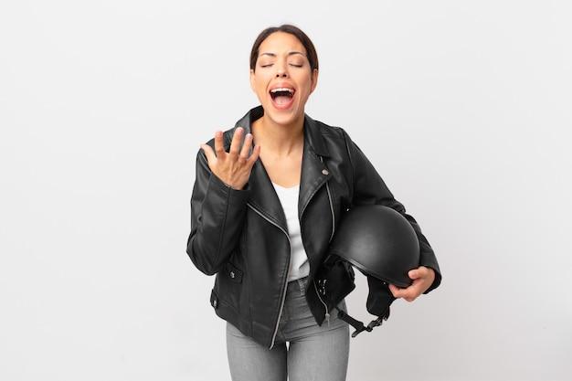 Junge hispanische frau, die verzweifelt, frustriert und gestresst aussieht. motorradfahrerkonzept