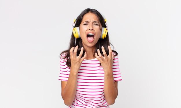 Junge hispanische frau, die verzweifelt, frustriert und gestresst aussieht und musik mit kopfhörern hört