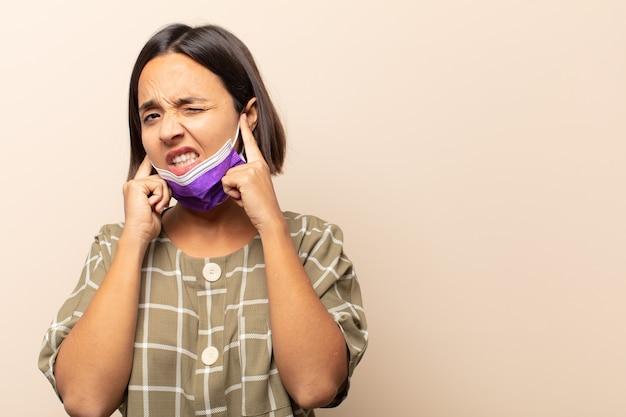 Junge hispanische frau, die wütend, gestresst und verärgert aussieht und beide ohren zu einem ohrenbetäubenden geräusch, ton oder lauter musik bedeckt