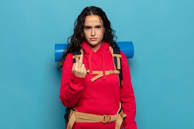 Junge hispanische frau, die wütend, verärgert, rebellisch und aggressiv ist, den mittelfinger bewegt und sich wehrt