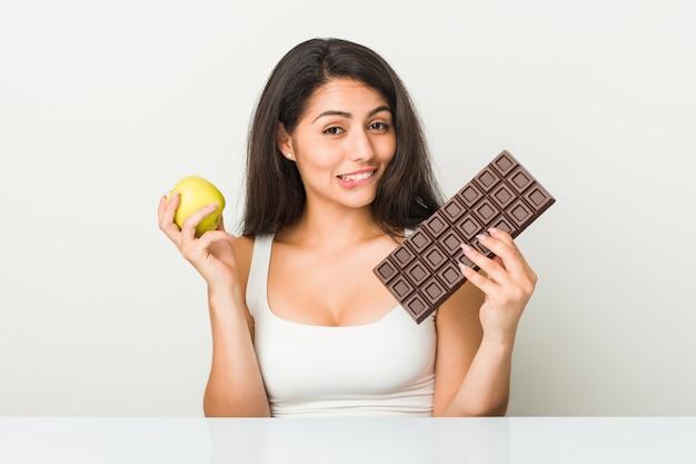 Junge hispanische frau, die zwischen apfel- oder schokoladentafel wählt